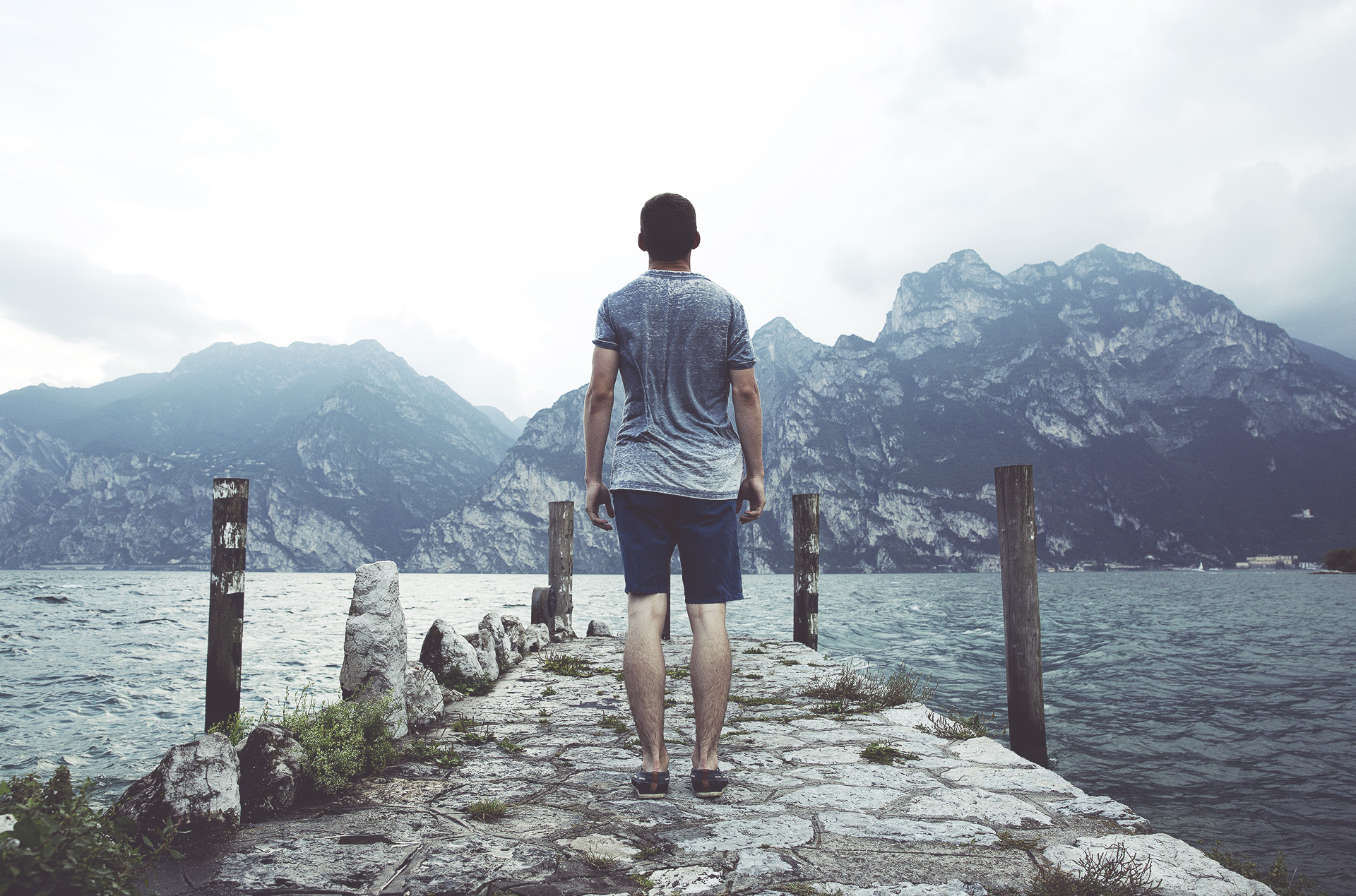 man standing on a pier overlooking water praying God will strengthen him