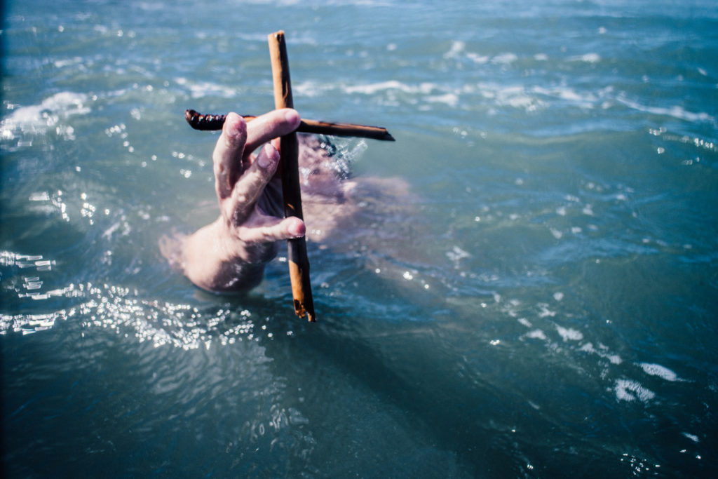 Man underwater but clinging to the cross of Grace